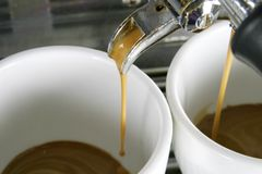 Two Cups Espresso. Detail image of two cups of espresso being made in an industrial profesional machine Stock Images
