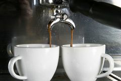 Two Cups Espresso. Detail image of two cups of espresso being made in an industrial profesional machine Royalty Free Stock Photo