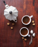 Two cups of espresso with pieces of cane sugar and Italian  coffee maker. Stock Photo