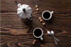 Two cups of espresso with pieces of cane sugar and Italian  coffee maker on  table. Stock Photos