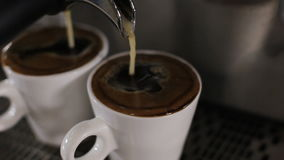 Two cups of espresso pour out. Close up stock video
