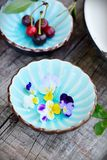 Two cups with flowers and cherry Stock Photography
