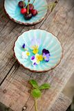 Two cups with flowers and cherry Stock Photos