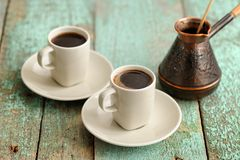 Two cups of fresh black coffee and copper cezve on old wooden ta Royalty Free Stock Photo