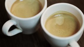 Two cups of fresh cooked coffee. Man hand straightens one cup. stock video footage
