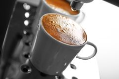 Two cups with fresh espresso in new coffee maker,. Closeup stock images