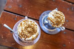 Two cups of fresh hot chocolate topped with whipped cream and salted caramel on a brown wooden table. stock images