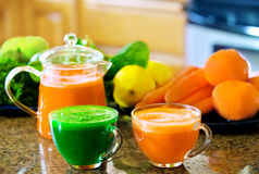 Two cups of fresh vegetable juice on kitchen counter with vegeta Royalty Free Stock Images