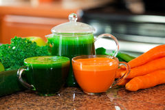 Two cups of fresh vegetable juice on kitchen counter with vegeta Stock Photography