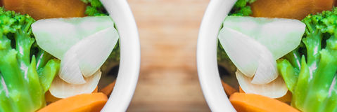 Two cups with fresh vegetables: carrots, broccoli, onions, potatoes. Panoramic shot. Royalty Free Stock Image