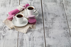 Two cups of freshly brewed espresso coffee. With macaroons on a textured wooden table top with copyspace Stock Photography