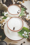 Two cups of freshly brewed, frothy cappuccino. Spilled coffee grains, chocolate and cane sugar. Theme of coffee, cappuccino, mocha chino, america no. Beautiful Stock Photo
