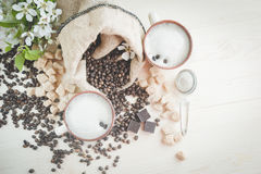 Two cups of freshly brewed, frothy cappuccino. Spilled coffee grains, chocolate and cane sugar. Theme of coffee, cappuccino, mocha chino, america no. Beautiful Stock Photos