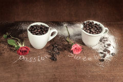 Two cups full of coffee beans with red bud rose on wooden table. Two cups full of coffee beans with grinded coffee,some sugar and roses of different colors on royalty free stock photography