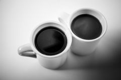 Two cups full of coffee stand on a table Royalty Free Stock Image
