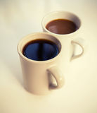 Two cups full of coffee stand on the table Stock Photos