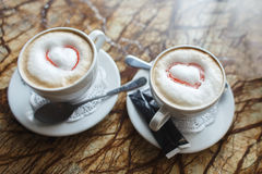 Two cups of gourmet coffee house cappuccino against on table Royalty Free Stock Photography