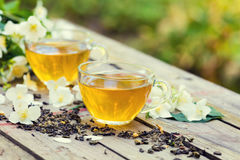 Two cups of green tea with jasmine flowers. On grunge wooden table outdoors Royalty Free Stock Photos