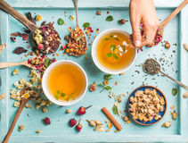 Two cups of healthy herbal tea with mint, cinnamon, dried rose, camomile flowers in spoons and man's hand holding spoon Royalty Free Stock Image