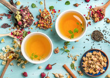 Two cups of healthy herbal tea with mint, cinnamon, dried rose and camomile flowers in spoons over blue background Royalty Free Stock Photos