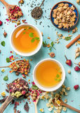 Two cups of healthy herbal tea with mint, cinnamon, dried rose and camomile flowers in spoons over blue background Stock Photos