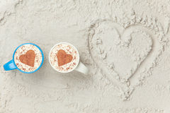 Two cups and heart shape symbol. Two cups of Cappuccino and heart shape symbol on sand Royalty Free Stock Photography