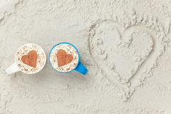 Two cups and heart shape symbol. Two cups of Cappuccino and heart shape symbol on sand Royalty Free Stock Photos