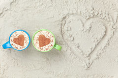 Two cups and heart shape symbol. Two cups of Cappuccino and heart shape symbol on sand Stock Photos