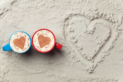 Two cups and heart shape symbol. Two cups of Cappuccino and heart shape symbol on sand Royalty Free Stock Image
