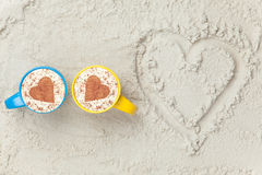 Two cups and heart shape symbol. Two cups of Cappuccino and heart shape symbol on sand Stock Photography