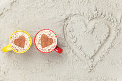 Two cups and heart shape symbol. Two cups of Cappuccino and heart shape symbol on sand Royalty Free Stock Photo