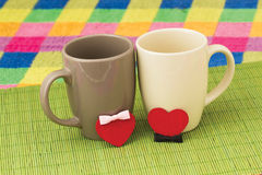 Two cups and hearts with bows. Symbols of hearts with bows and cups on a bamboo napkin on a color checkered background Stock Photos