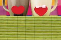 Two cups and hearts with bows. Symbols of hearts with bows and cups on a bamboo napkin on a color checkered background Royalty Free Stock Photography