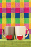 Two cups and hearts with bows. Symbols of hearts with bows and cups on a bamboo napkin on a color checkered background Stock Photo