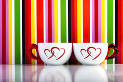 Two cups with hearts on colorful stripes background stock image