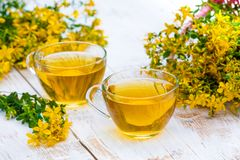 Two cups of herbal tea with tutsan. Two cups of herbal tea on the grunge wooden table Stock Photos