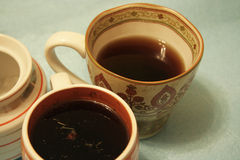Two cups with herbal tea and a sugar-bowl on the light-blue background. Две кружки с чаем и сахарница Stock Photography