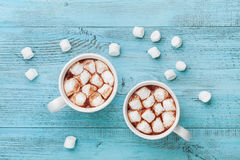 Two cups of hot chocolate on blue rustic table from above. Delicious winter drink. Flat lay. Royalty Free Stock Image
