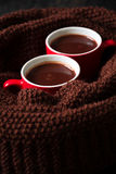 Two cups of hot chocolate. On brown knitted scarf Stock Photo