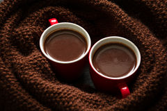 Two cups of hot chocolate. On brown knitted scarf Royalty Free Stock Photo
