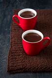 Two cups of hot chocolate. On brown knitted scarf Stock Photography