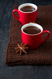 Two cups of hot chocolate. On brown knitted scarf Stock Images