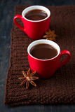 Two cups of hot chocolate. On brown knitted scarf Royalty Free Stock Photos