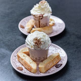 Two cups with hot chocolate garnish, whipped cream, cocoa powder, toasts, leaves of bitter chocolate Royalty Free Stock Photography