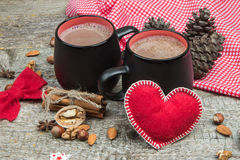 Two cups of hot chocolate and red heart on wooden background Stock Images