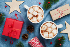 Two cups of hot cocoa or chocolate with marshmallow, gift box, christmas decor and fir tree on knitted blue background from above. Royalty Free Stock Photos