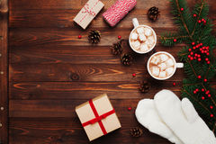 Two cups of hot cocoa or chocolate with marshmallow, gifts, mittens, christmas decor and fir tree on wooden background above. Stock Photography
