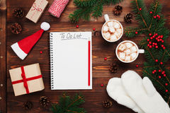 Two cups of hot cocoa or chocolate with marshmallow, gifts, mittens, christmas fir tree and notebook with to do list. Flat lay.