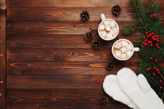 Two cups of hot cocoa or chocolate with marshmallow, mittens, christmas decor and fir tree on wooden rustic background from above. Royalty Free Stock Photography