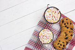 Two cups of hot cocoa with color marshmallow and oatmeal cookie royalty free stock image
